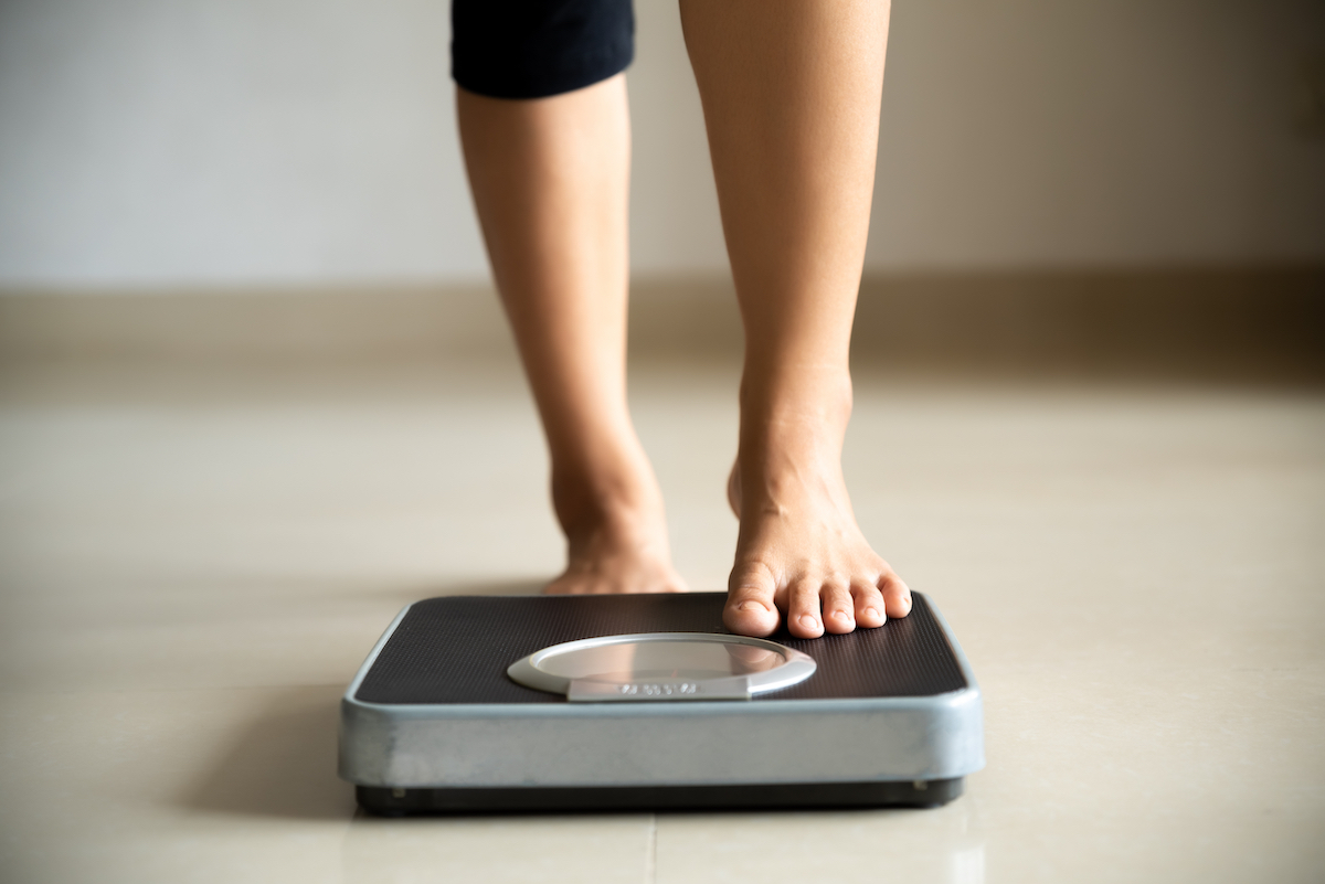 Woman stepping on a scale